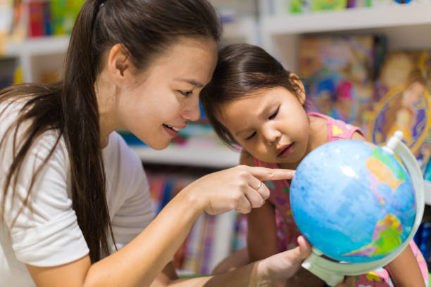 A teacher and a preschool student learning geography on a world globe A parent teaching her child on a map about the continents and countries in the library bookstore. country geographic area stock pictures, royalty-free photos & images