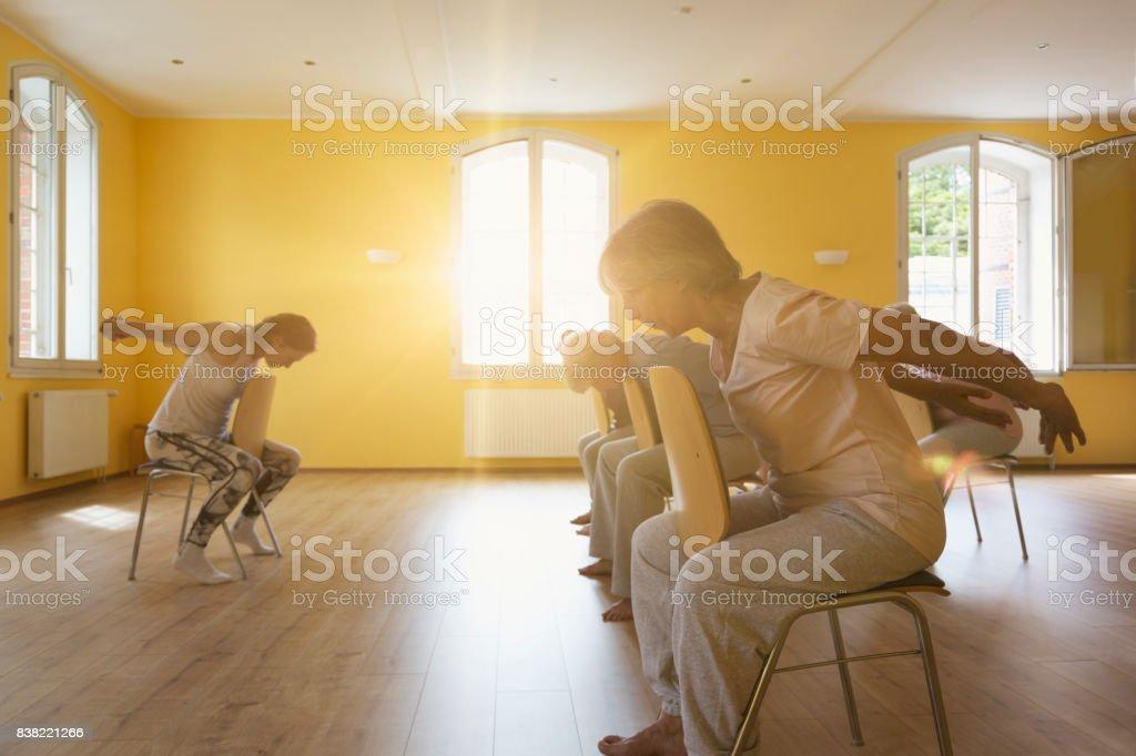 Teacher and active senior women doing yoga class on chairs stock photo