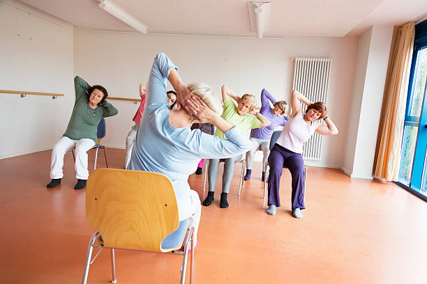 teacher and active senior women yoga class on chairs - stoel stockfoto's en -beelden
