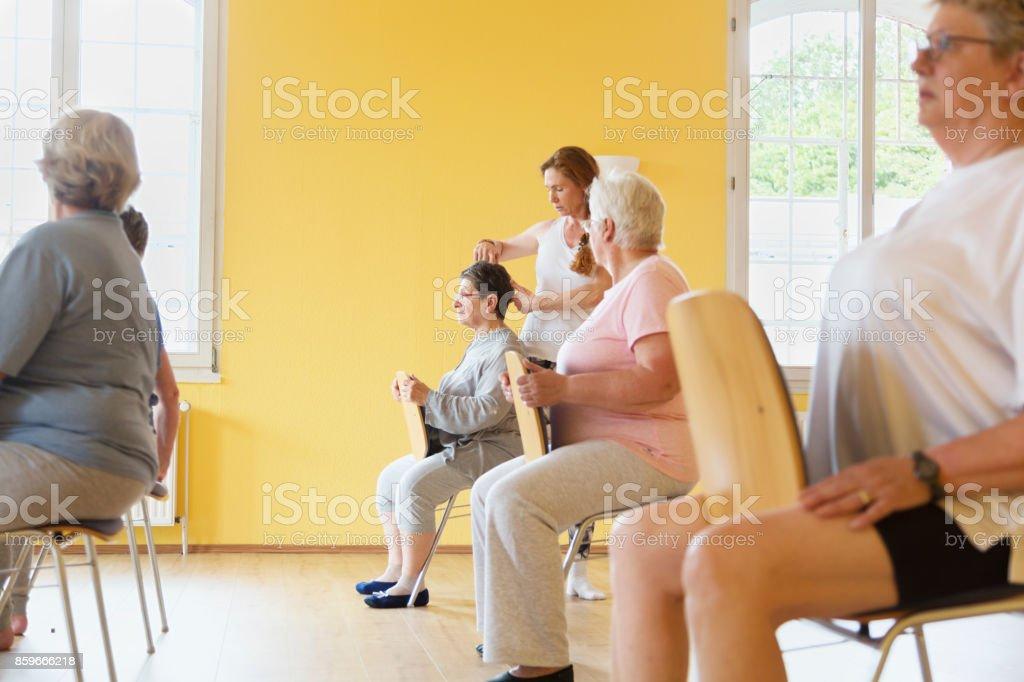 Teacher and active senior women yoga class on chairs stock photo