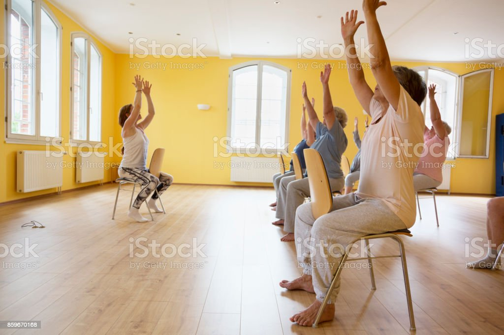 Teacher and active senior women yoga class on chairs Teacher and active senior women yoga class on chairs, arms raised, 60-69 Years Stock Photo