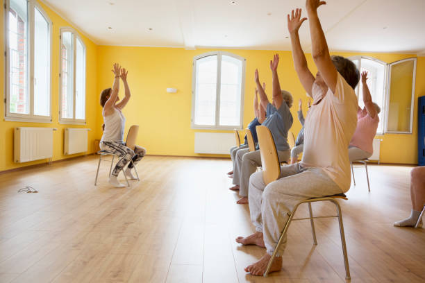 teacher and active senior women yoga class on chairs - relaxation exercise stock photos and pictures