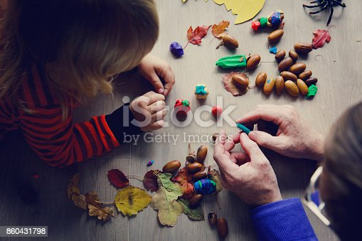 istock Teacher and child making crafts from clay and natural materials for Halloween 860431798