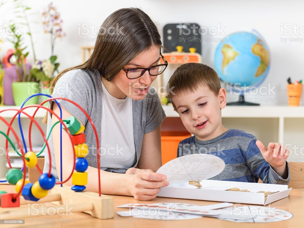 Teacher and Child Playing at Kindergarten Didactic Games stock photo