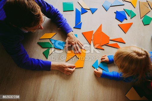 istock teacher and child playing with geometric shapes 852032238