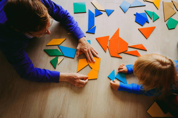 teacher and child playing with geometric shapes stock photo