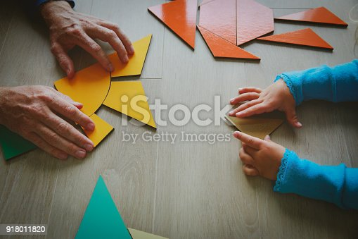 istock teacher and child playing with geometric shapes 918011820