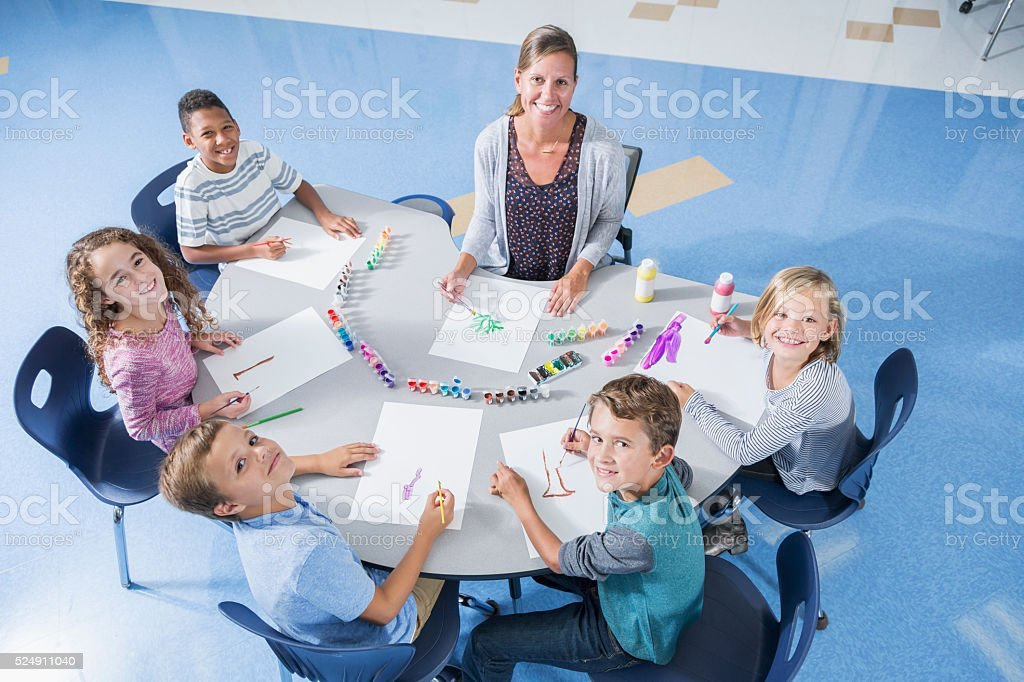 High angle view of a female teacher and five elementary school...