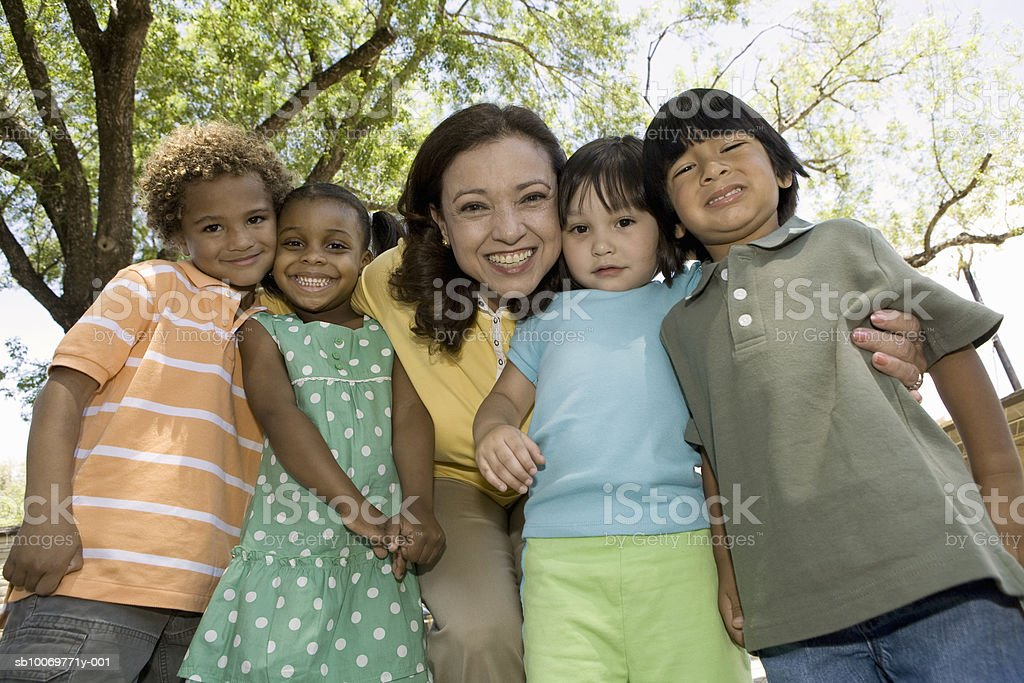 Teacher and children (2-5) in garden, low angle view foto de stock libre de derechos