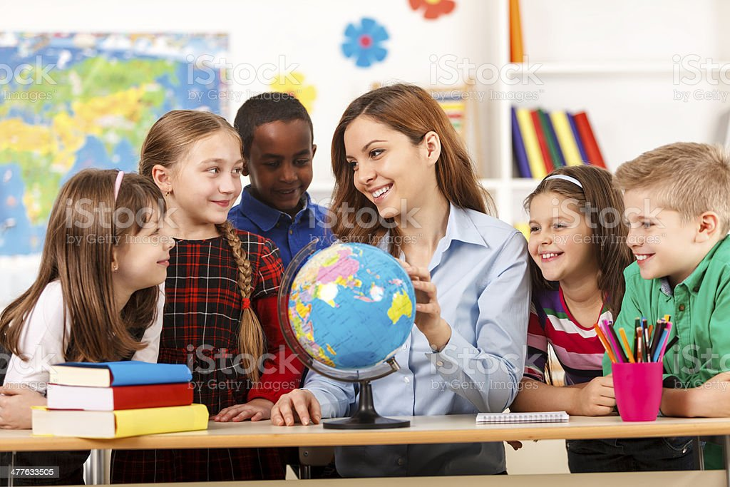 Teacher and children looking at globe stock photo