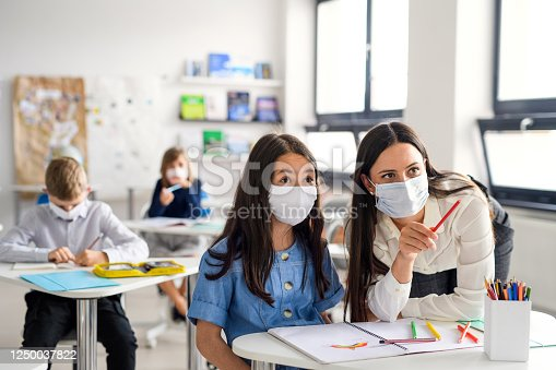 Teacher and children with face mask back at school after covid-19 quarantine and lockdown, explaining.