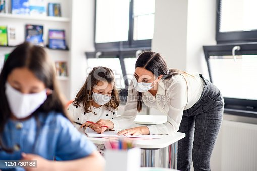 Teacher and children with face mask back at school after covid-19 quarantine and lockdown, writing.