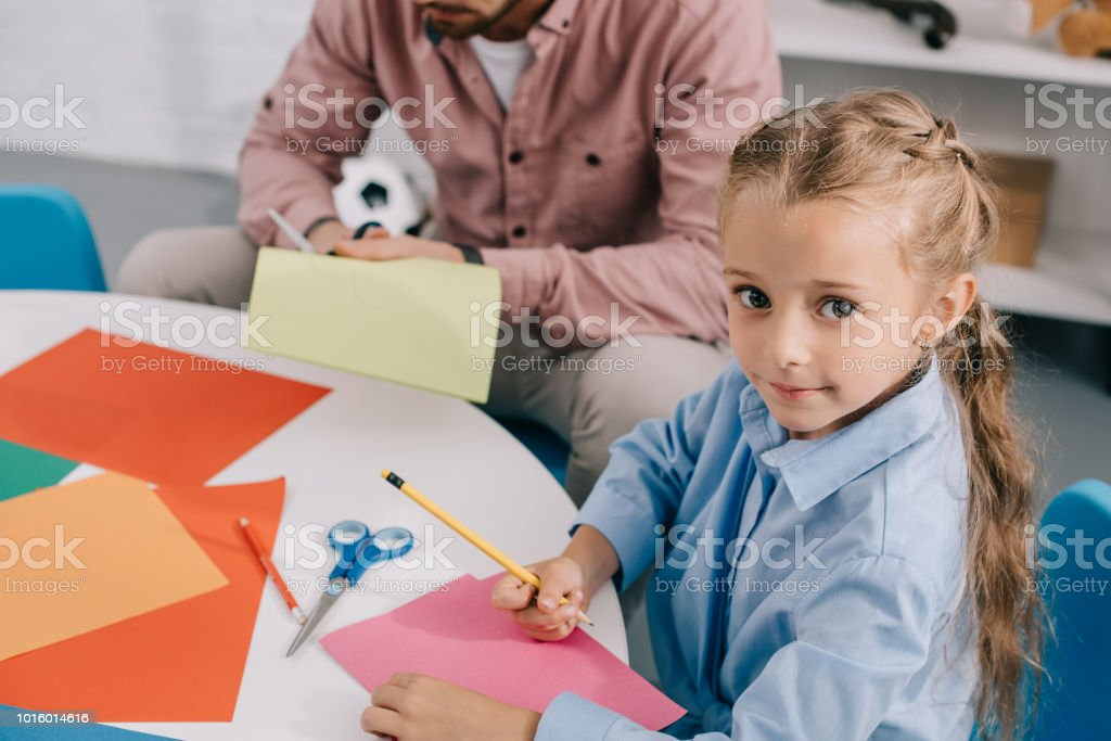 teacher and cute preschooler cutting papers with scissors att able in classroom stock photo