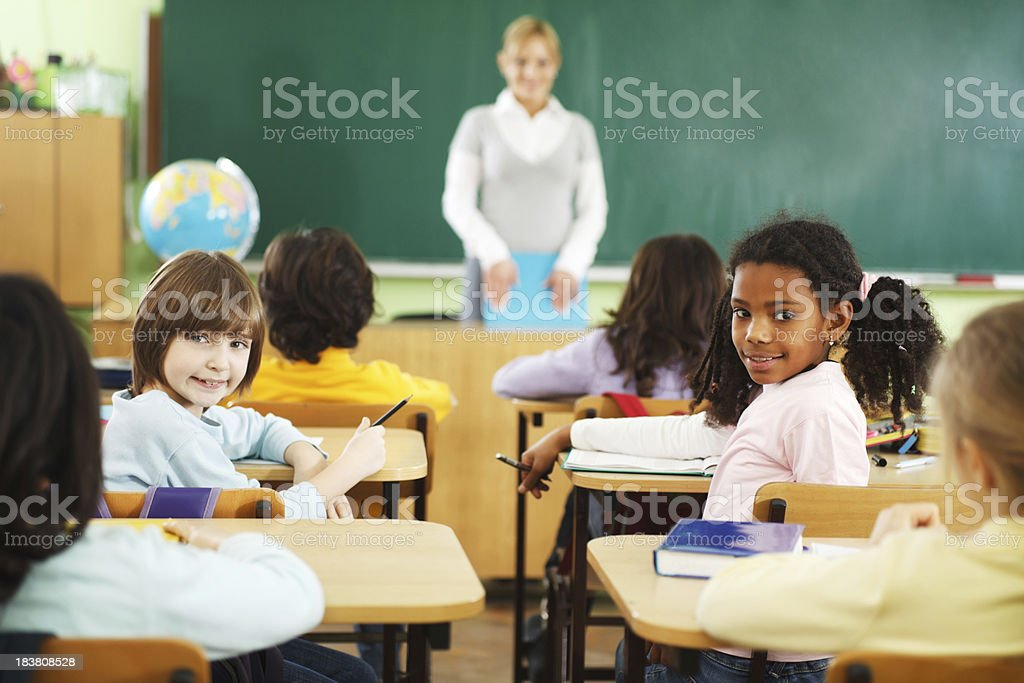 Teacher and elementary students in a classroom. royalty-free stock photo