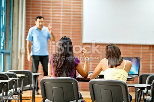 481711196istockphoto Teacher and female students using wireless laptop computer in classroom 692537582