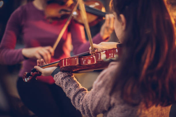 Teacher and girl playing violins together Two people, woman violin teacher working with little boy on violin lessons. string instrument stock pictures, royalty-free photos & images