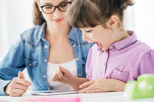 School teacher and girl using a digital tablet, education and technology concept