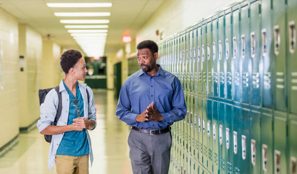Teacher and high school student walking in hallway An African-American high school student walking with his teacher or school principal, in the hallway by a row of lockers. They are talking. The teacher has a serious expression on his face, a mature man in his 50s. The male student is an 18 year old teenage boy carrying a backpack. high school teacher stock pictures, royalty-free photos & images