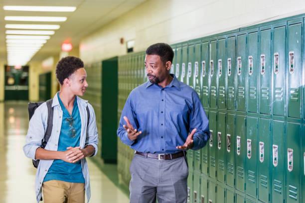Teacher and high school student walking in hallway stock photo