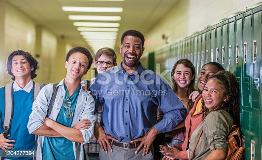 A multi-ethnic group of six high school students, 15 to 18 years old, hanging out together in the hallway by the lockers, between classes, with the teacher or school principal, a mature African-American man in his 50s. They are smiling at the camera.