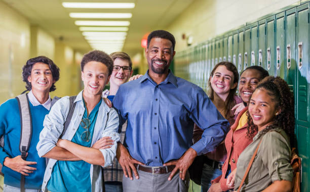 Teacher and high school students hanging out in hallway stock photo
