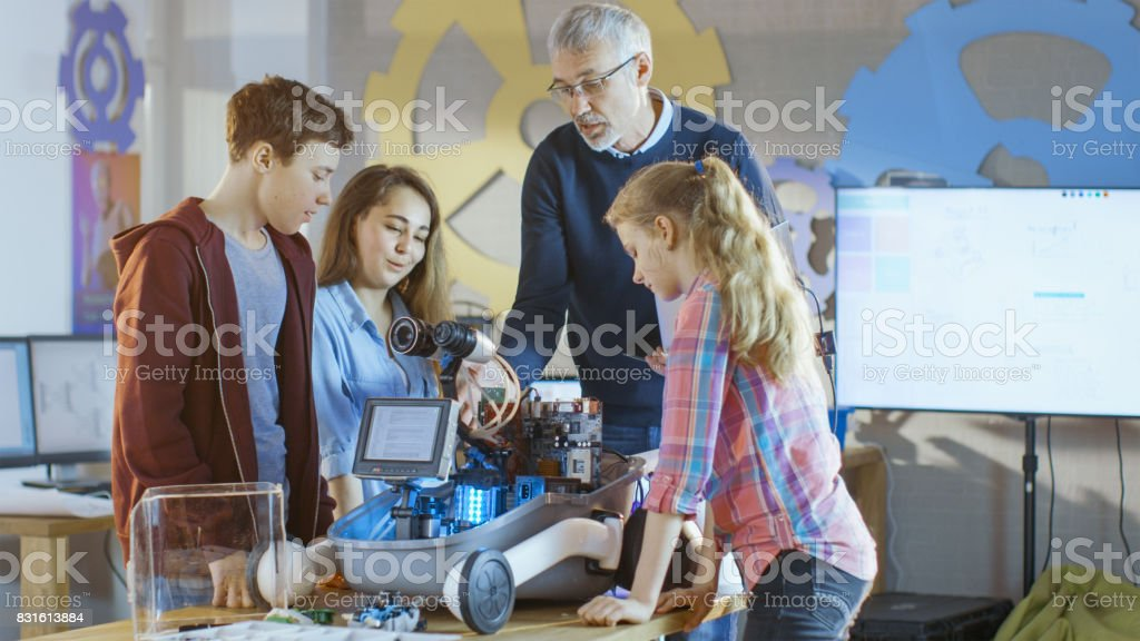 Teacher and His Pupils Work on a Programable Robot with LED Illumination for School Science Class Project. stock photo