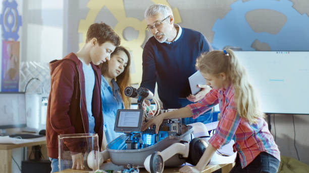 lehrer und seine schüler arbeiten an einem programmierbaren roboter mit led-beleuchtung für schule wissenschaft klassenprojekt. - versuche nicht zu lachen stock-fotos und bilder