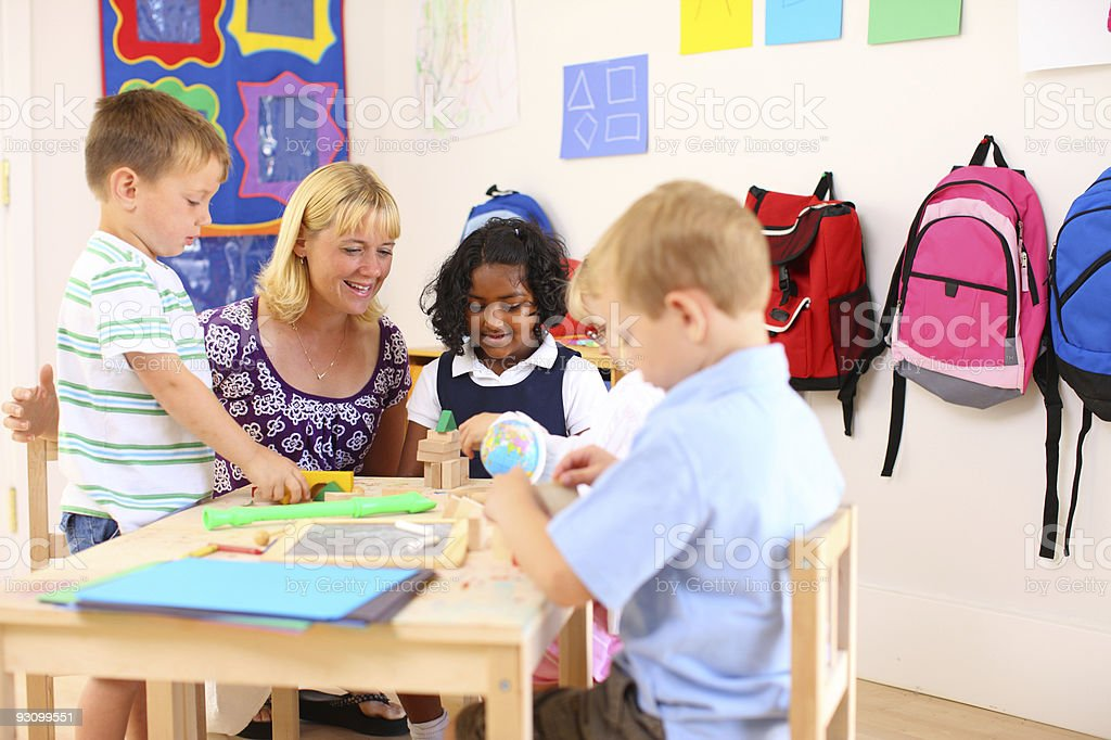 Teacher and kids in preschool classroom royalty-free stock photo