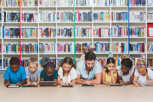 Teacher and kids lying on floor using digital tablet stock photo