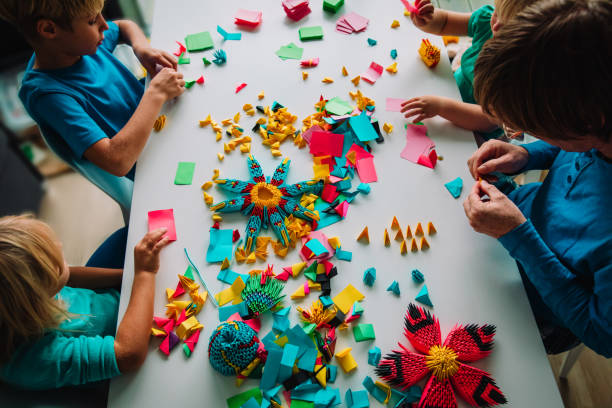 teacher and kids making origami crafts with paper - art and craft stock pictures, royalty-free photos & images