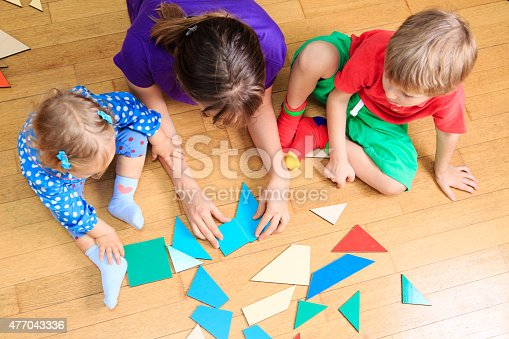 istock teacher and kids playing with geometric shapes 477043336