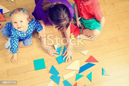 istock teacher and kids playing with geometric shapes 486254134