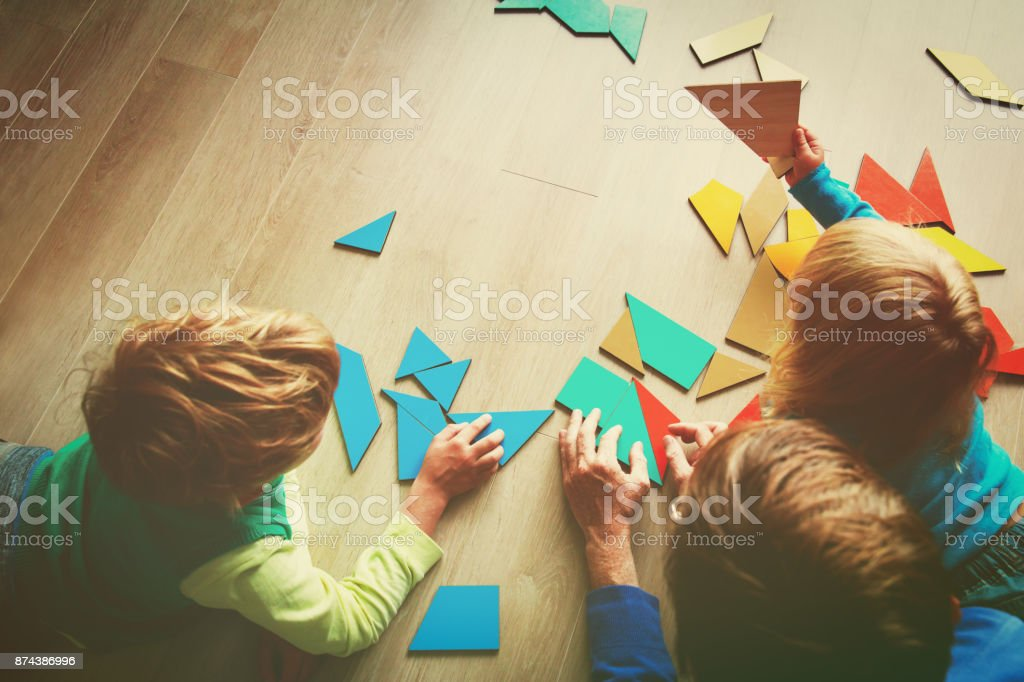 teacher and kids playing with geometric shapes stock photo