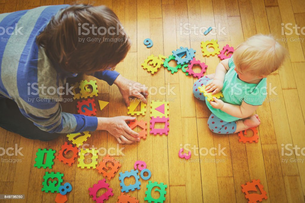 teacher and little baby playing with number puzzle stock photo