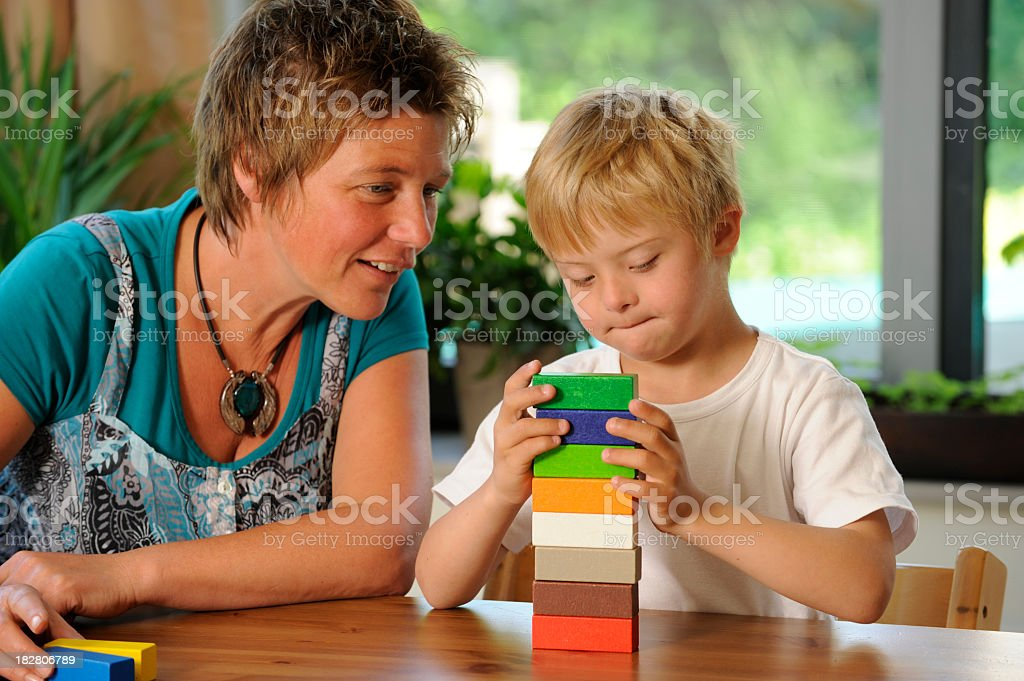 Teacher and pupil building colored blocks stock photo
