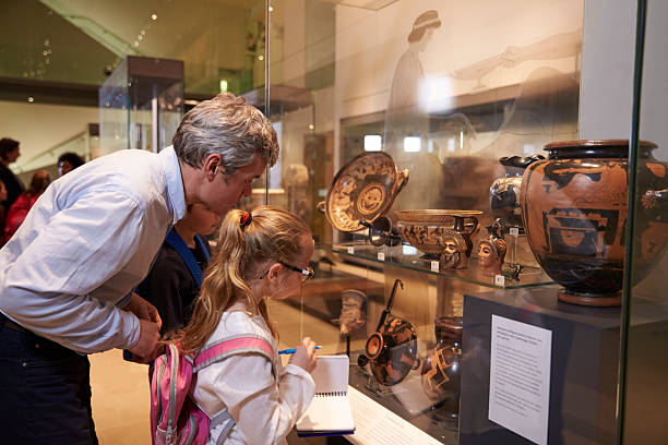 teacher and pupils looking at artifacts on display in museum - museum stockfoto's en -beelden