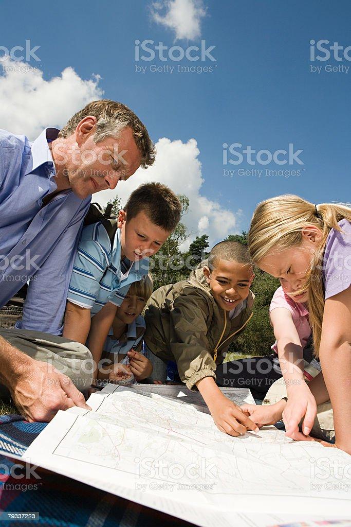 Professor e alunos olhando no mapa - foto de acervo
