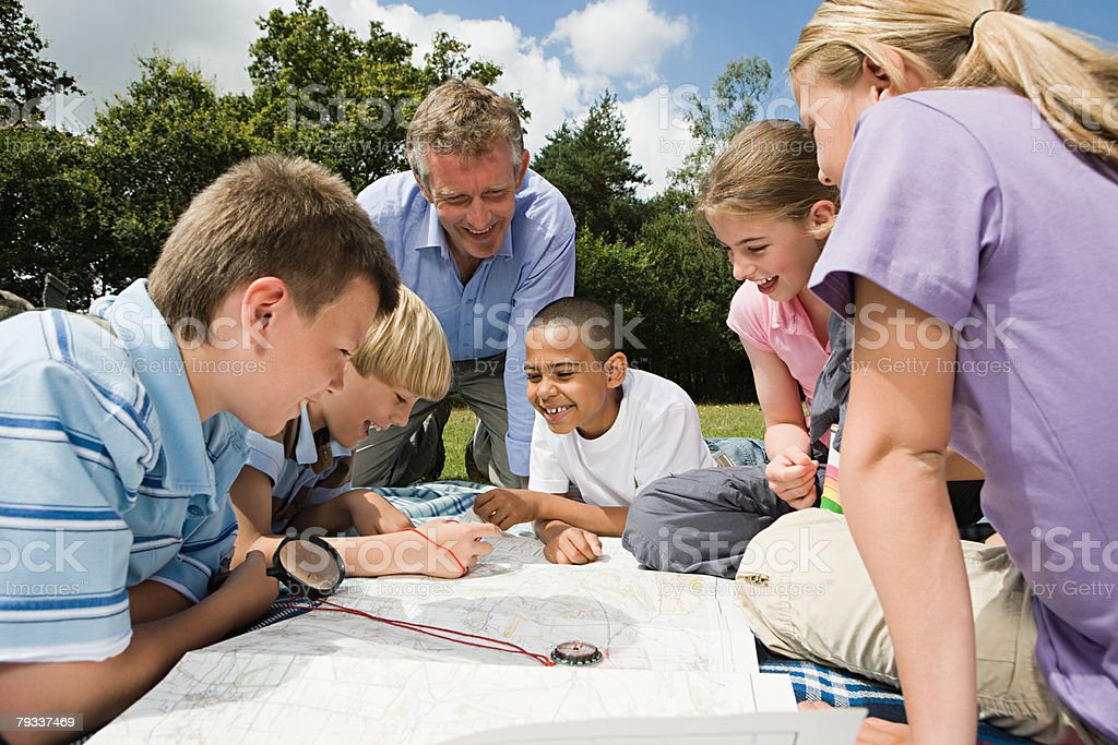 Teacher and pupils looking at map stock photo