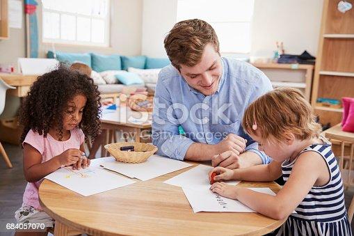 684059604 istock photo Teacher And Pupils Practicing Writing In Montessori School 684057070