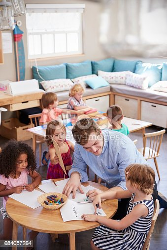 684059604 istock photo Teacher And Pupils Practicing Writing In Montessori School 684057264