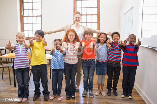 istock Teacher and pupils smiling at camera in classroom 472662586