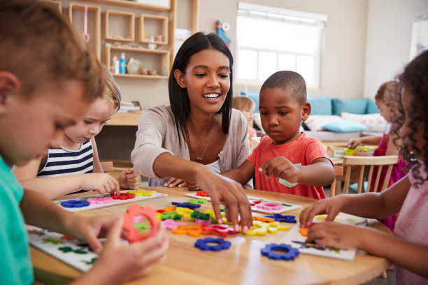 teacher and pupils using flower shapes in montessori school - preschool stock photos and pictures