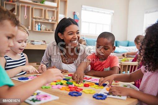 684059604 istock photo Teacher And Pupils Using Flower Shapes In Montessori School 684061674