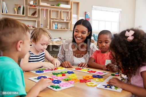 684059604 istock photo Teacher And Pupils Using Flower Shapes In Montessori School 684061684