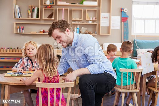 istock Teacher And Pupils Using Wooden Shapes In Montessori School 684057124
