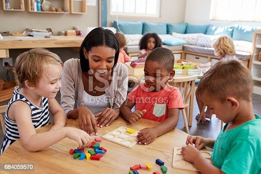 istock Teacher And Pupils Using Wooden Shapes In Montessori School 684059570