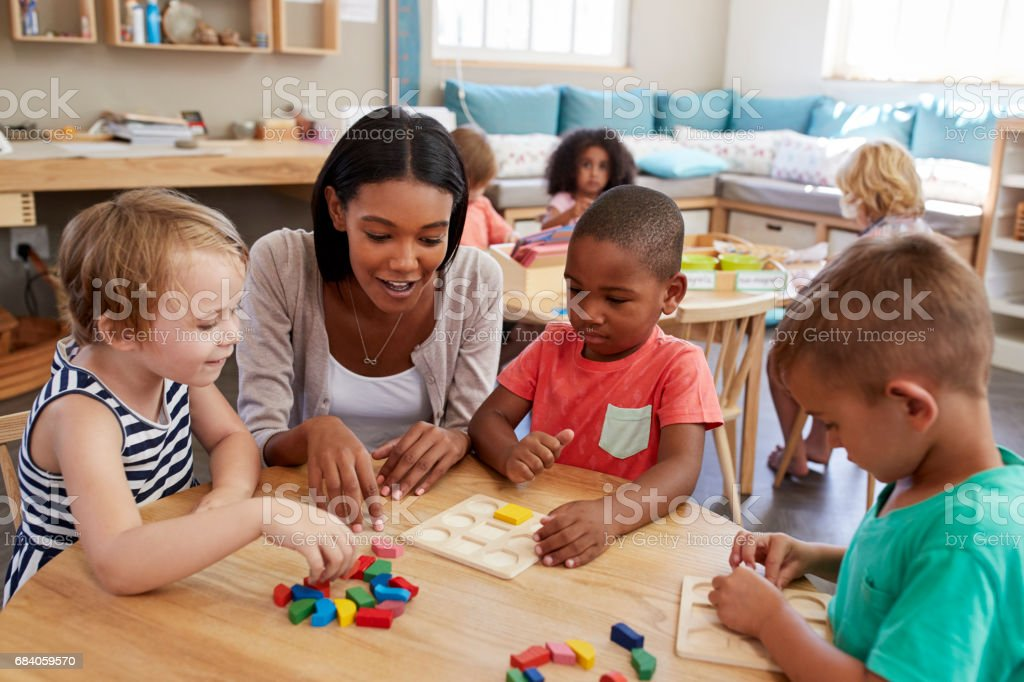 Teacher And Pupils Using Wooden Shapes In Montessori School stock photo