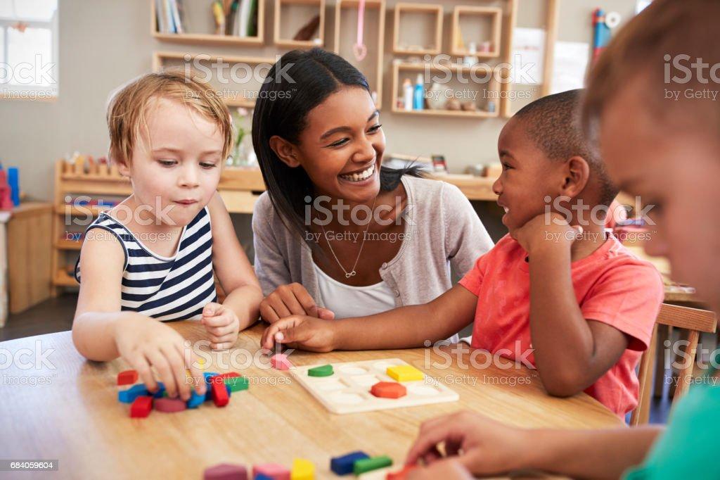 Lehrer und Schüler mit Holzformen in Montessori-Schule - Lizenzfrei Lehrkraft Stock-Foto