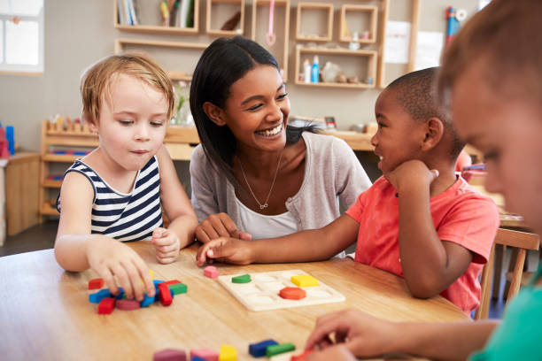 teacher and pupils using wooden shapes in montessori school - preschool stock photos and pictures