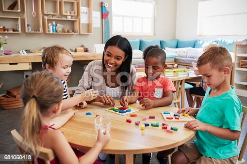 istock Teacher And Pupils Using Wooden Shapes In Montessori School 684060418